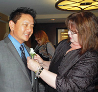 Elizabeth J. Clark puts boutineer in Marshall Wong's buttonhole