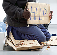 person's lower body in warm clothing kneeling on cardboard with a 'HELP' sign