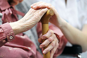 older female hands with younger female hand on cane