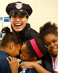 female cop being hugged by several girls