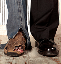 man's legs: left with torn jeans and broken down shoe; right with wool dress pant and polished black shoe