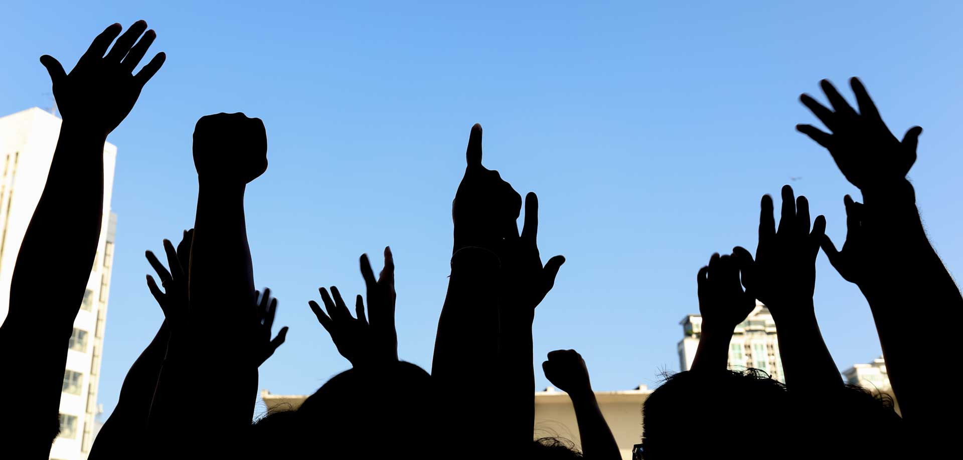 group of people in silhouette with hands raised in the air