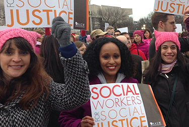 group of people at a protest march, with signs that say Social Workers for Justice