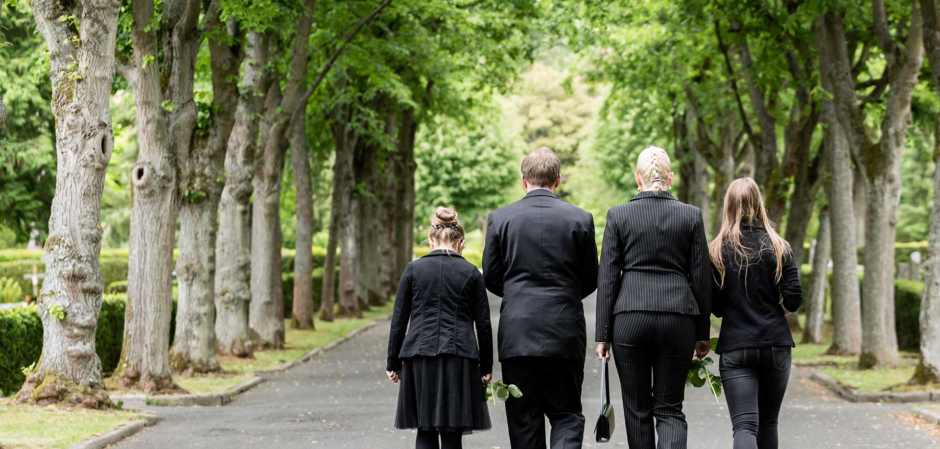 family of four dressed in black clothing walk down path away from camera