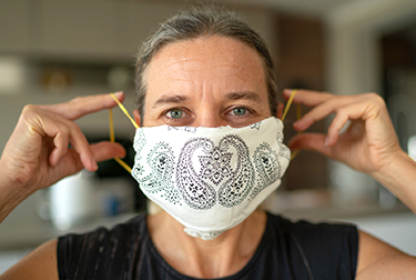 woman in an office puts on face mask