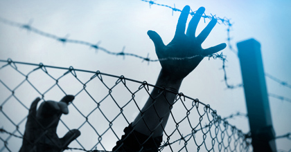 hands grasping chain link fence