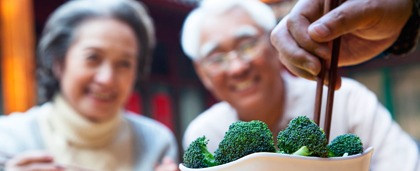 bowl of broccoli, chopsticks, smiling man and woman in background