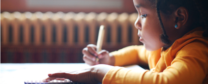young child writing at a desk