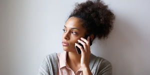 worried looking woman holding a cell phone