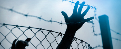 hand reaches over chain link fence and barbed wire