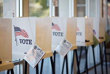 voting booths, signs with United States flag and the word vote