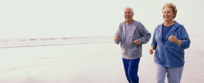older couple jogging on the beach