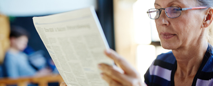 woman in glasses reads a newspaper