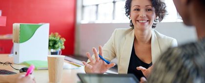 smiling woman at a work table talks with a colleague