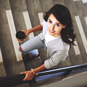 woman walks up stairs with coffee cup