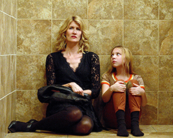 The Tale - woman (Laura Dern) sits on floor next to a young girl with their backs against a wall