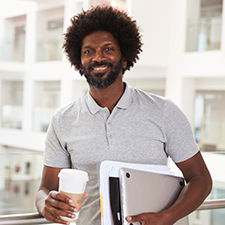 man with beard holds tablet, coffee