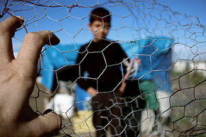 child behind chicken wire fence