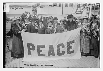 archival photo of women holding a fabric sign that reads Peace
