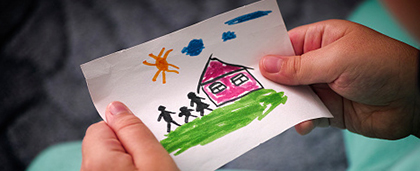child holds drawing of house and family