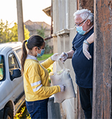 young adult delivering supplies to older man with gloves, protective face masks