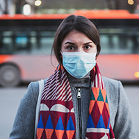 woman stands outside wearing a face mask