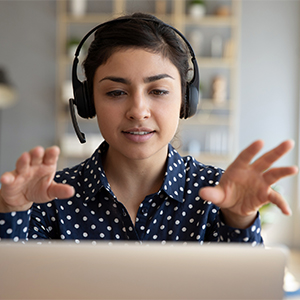 woman wearing a headset looks at laptop, gestures with both hands