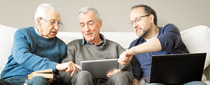 senior man showing media to friends on tablet