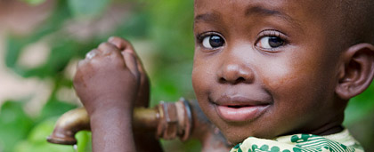 smiling little kid standing by a water spigot