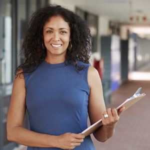 woman with clipboard stands in school hallway