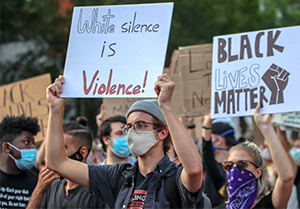 protesters holding signs: white silence is violence and black lives matter