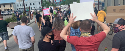 group of protesters marching with signs in Fairbanks, Alaska