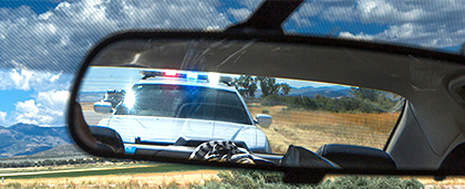 police car seen in rearview mirror