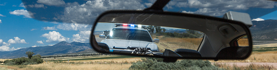 driver's view of police car in rear view mirror