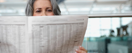 woman reads newspaper at an airport